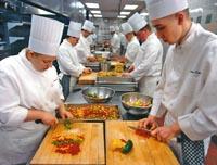 mindestens sechs Köche sind zu sehen, aufgereiht wie sie Gemüse auf Schneidbrettern für die Gerichte kleinschneiden