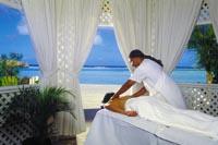 eine Person wird in einem weißen Pavillon direkt am Strand massiert