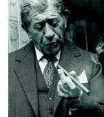 Ein älterer Herr im Anzug geniesst seine Zigarre