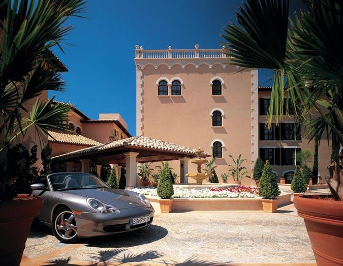 Ein Haus im Spanischen Kolonialstil und dessen Einfahrt, in der ein Porsche Cabrio parkt