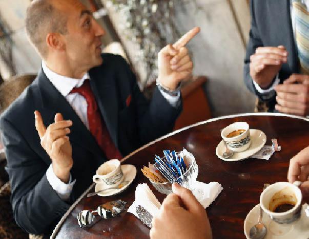 eine Herrenrunde bei Kaffee auf einem kleinen Bistrotisch