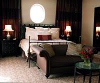 ein Bett in einem Hotel, mit weißer Bettwäsche und einem braunen Ledersofa davor