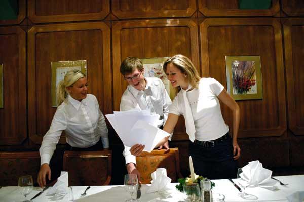 zwei Damen und ein Herr decken gemeinsam eine Tafel ein und gehen dabei ein schriftliches Protokoll durch