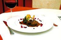 ein gedeckter Tisch, ein Glas Rotwein und eine Wildkreation auf dem Teller