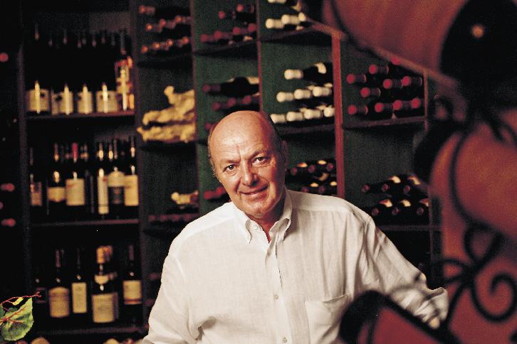 ein älterer Herr steht in einem Weinkeller vor einigen Regal befüllt mit diversen Flaschen
