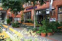 ein uriges aus rotem ziegelstein und hinter grünen büschen verstecktes restaurant mit einem schanigarten