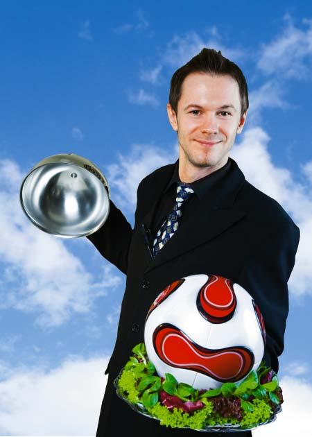 Ein Mann im Anzug öffnet die Cloche und darunter befindet sich ein Fußball auf Salat