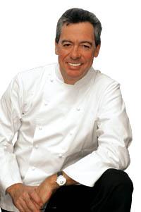 Philippe Rochat hockt in Kochuniform und grinst in die Kamera