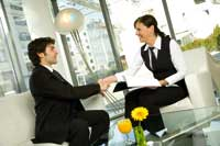 eine Dame und ein Herr sitzen bei einer Besprechung und geben sich einen Händedruck