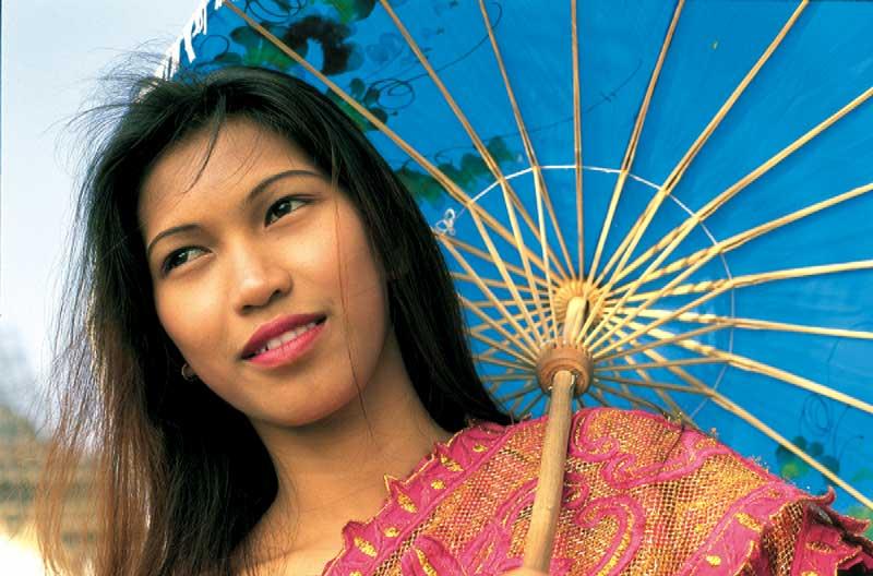 eine vietnamesische frau bunt gekleidet mit einem Sonnenschirm