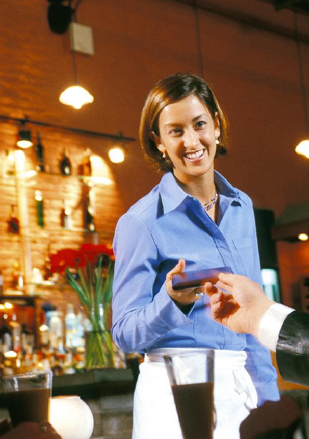 Kellnerin nimmt vom Kunden die Karte zum zahlen entgegen