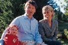 Eine junge Familie, Mutter Vater und Kleinkind lächeln fröhlich