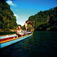 ein Paar sitzt in einem Holzboot und genießt die Sonnenstrahlen