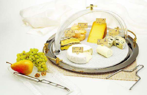 eine Kombosition verschiedener Käsesorten unter einer käseglocke mit weintrauben und birnen