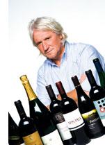 ein Mann hinter einer Reihe von verschiedensten Weinflaschen