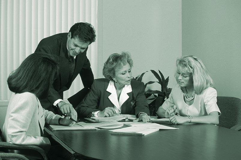 Ein Business Meeting in einem Konferenzraum bestehend aus einem stehenden Mann und drei sitzenden Frauen