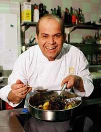 Hans-Peter Fink lächelt hinter einem Topf mit Fleisch