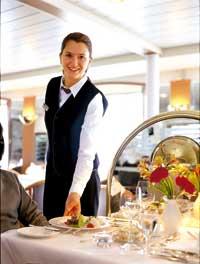 eine Kellnerin lächelt in die Kamera während sie einem Herrn das Gericht serviert