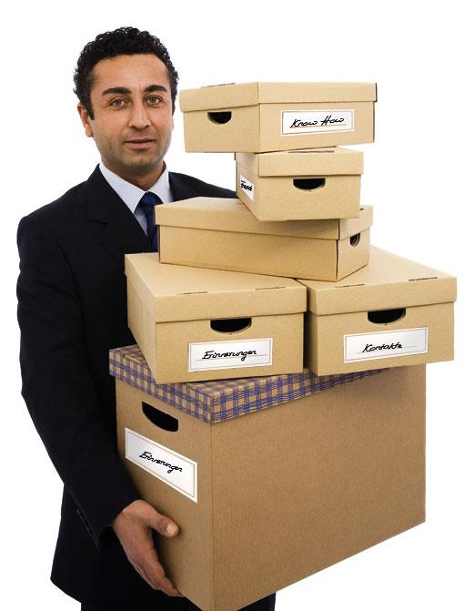 Ein Herr vollbepackt mit Kartons in verschiedenen Größen nach einer Kündigung