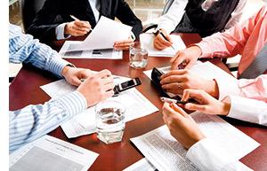 ein Blick in die Mitte des Konferenztisches, viel Papierkram, viele Hände die Notizen schreiben