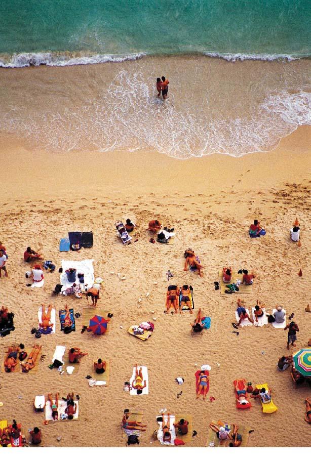 Sandstrand mit Menschen die sich sonnen und einem liebespaar im wasser