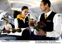 zwei Stewards an Board eines Flugzeuges mit roten Rosen