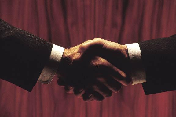 Handschlag zweier Männer, theatralisch vor einem roten Vorhang