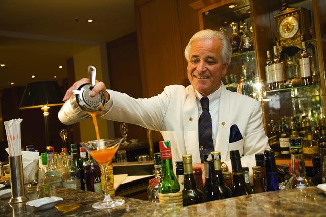 ein Barkeeper füllt den Cocktail vom Shaker ins Glas
