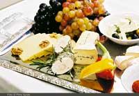 eine Käseplatte mit verschiedensten Sorten und Weintrauben darauf