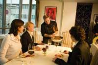 ein Kellner präsentiert einem Tisch mit zwei Damen und einem Herrn die Köstlichkeiten