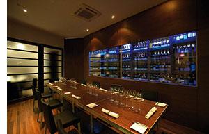 Saint Pierre Restaurant mit einer Vinothek aus Glas hinter einer langen Tafel