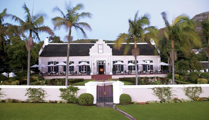 ein Haus mit einer weißen Hausmauer, dazwischen ein Biotop und viele Palmen die das Grundstück zieren