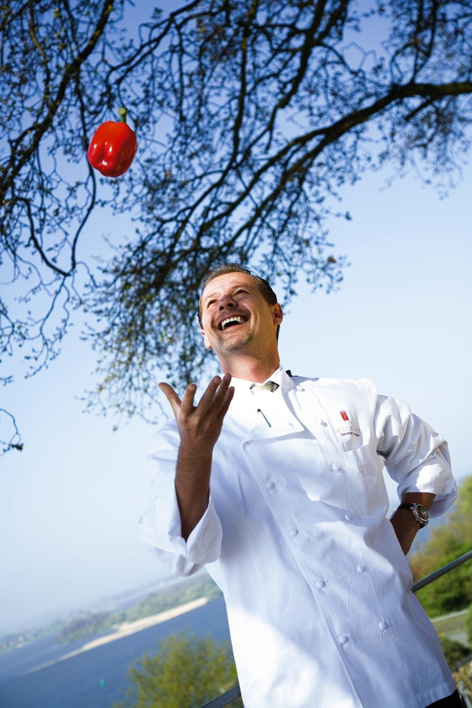 Karlheinz Hauser steht im Grünen und wirft roten Paprika in die Luft