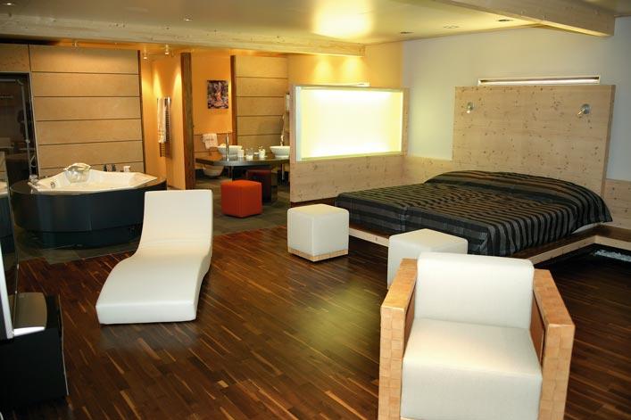 ein großes und offenes Hotelzimmer mit einem Kingsizebett und einer Whirlpool Badewanne