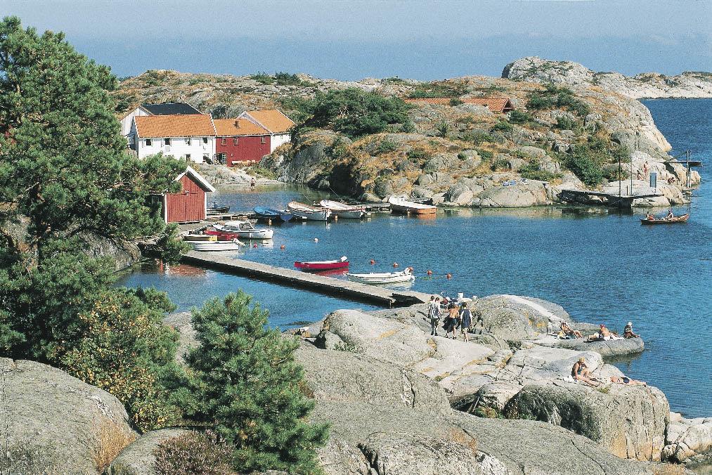 Norwegens Küste, ein langer Steg ins Wasser mit Holzbooten und Menschen beim Sonnenbaden