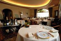 Ein Restaurant ist zu sehen, mit runden und gedeckten Tischen