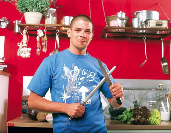 Tim Mälzer schärft ein Messer in der Küche