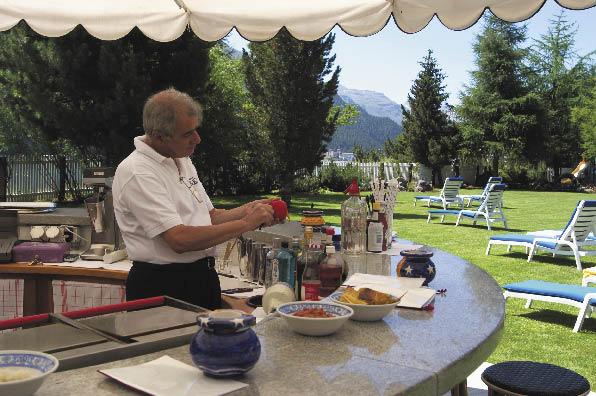 eine Bar inklusive Kellner, der eine Tomate schält, im Hintergrund sind Sonnenliegen auf der Wiese aufgestellt