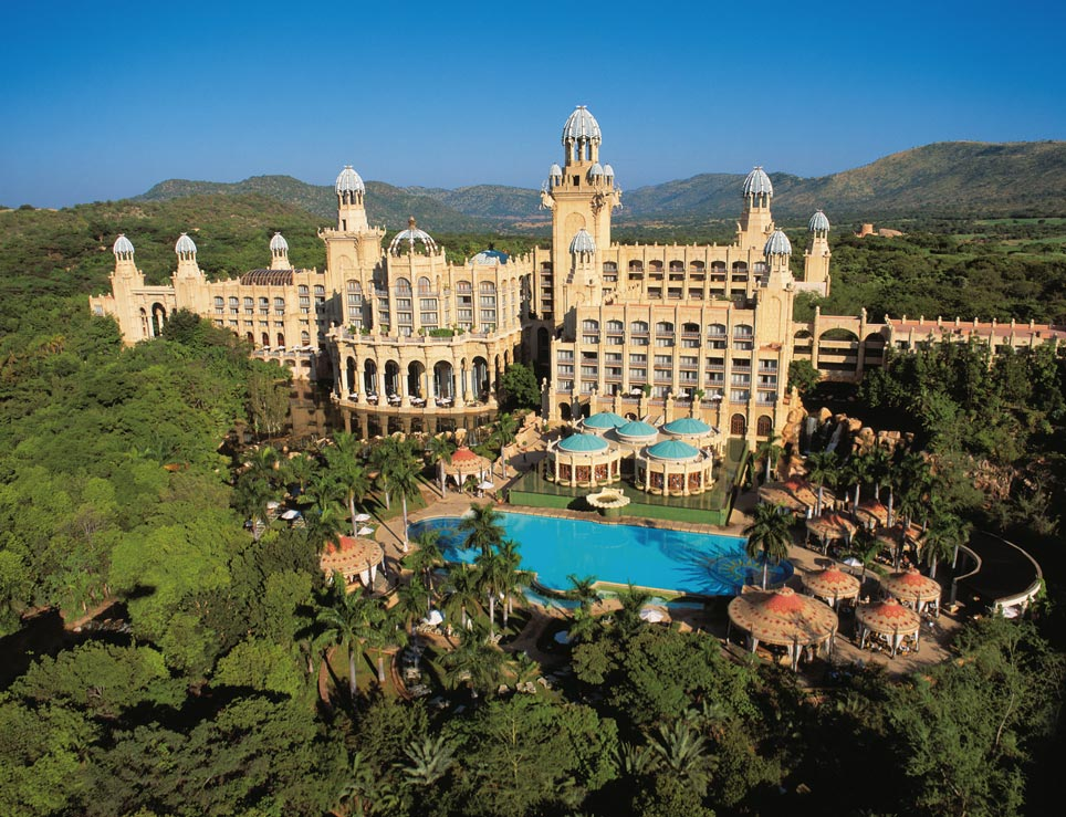 ein enormer Hotelkomplex inmitten einer grünen Berglandschaft mit Swimming Pool und großen Fenstern