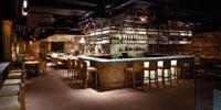 eine Bar aus Holz ist zu sehen, darum befinden sich Esstische mit freistehenden Stühlen