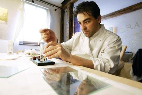 Juan Amador sitzt an einem Tisch und legt den Feinschliff an seiner Kreation an