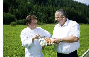 Gerhard Fuchs mit freilandeiern in der hand waehrend er sich mit einem zweiten mann unterhaelt