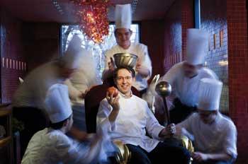 Heinz Reitbauer jun. sitzt in einer Art Thron umgeben von Köchen mit Utensilien der Küche