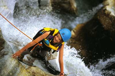 eine junge Frau betreibt Canyoning