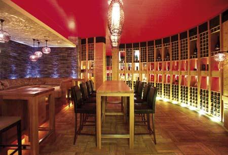 hohe Tische und Barhocker mit einer kräftigen roten Wand, davor ein Regalverbau für Weinflaschen
