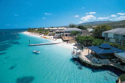 ein Hotelprivatstrand mit einem Steg ins türkisblaue Wasser führend in der Karibik
