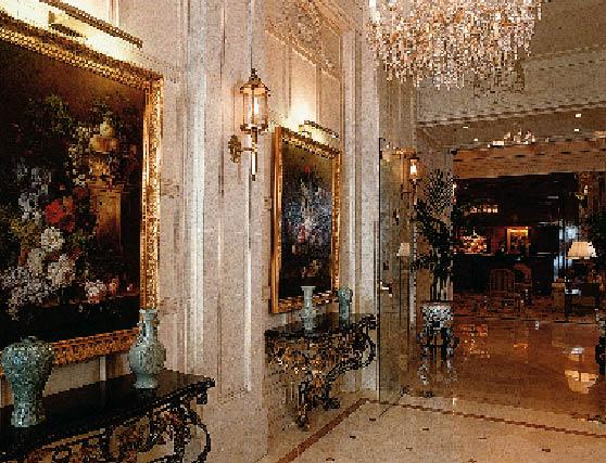 ein Raum mit französischen Möbeln ist zu sehen, an den Wänden hängen Gemälde von Blumenarragements und ein großer Kronleuchter ziert den Raum