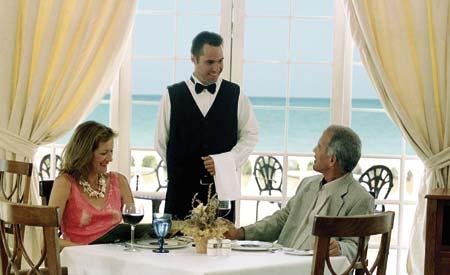 Ein Kellner begrüßt ein Paar am Esstisch mit Aussicht an den Stand