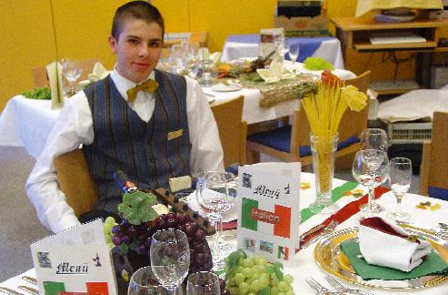 Ein junger Herr sitzt an einem Tisch vor ihm Weintrauben und Speisekarten