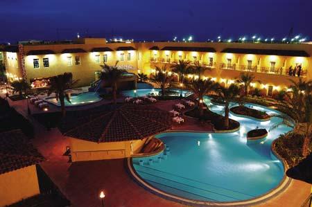 die Poolanlage eines Hotels in der Nacht mit dezenter Hintergrundbeleuchtung